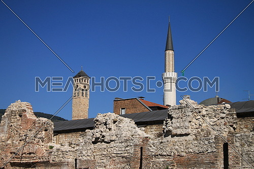 Clock tower and mosque minaret in old part of Sarajevo , Bosnia and Herzegovina