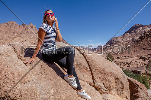 long shot for a female tourist siting on a rock explore Sinai Mountain for wadi Freij by day.
