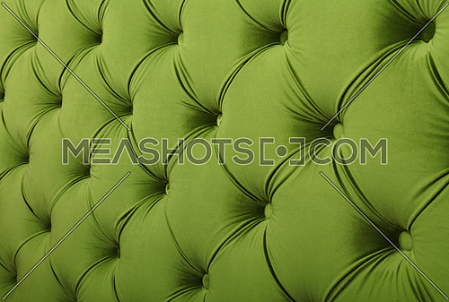 Green capitone textile background with buttons, retro Chesterfield style soft tufted fabric furniture upholstery diamond pattern decoration, close up