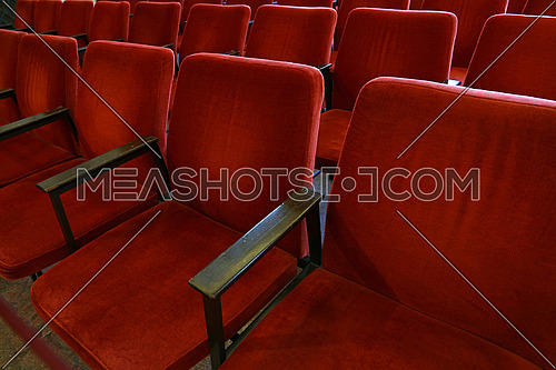 Close up red soft chair seats in a row, personal perspective, high angle view