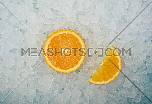 Close up one fresh juicy orange cut half and wedge slice over background of crushed ice, elevated high angle view, directly above
