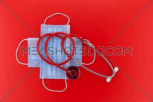 Crossed protective surgical face masks and stethoscope over a red background with copy space