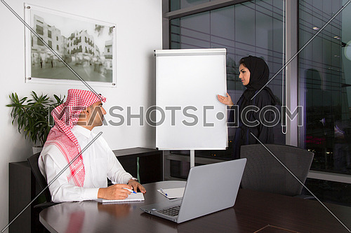 Two young people in Saudi tradition clothes Focusing in the meeting at the office.