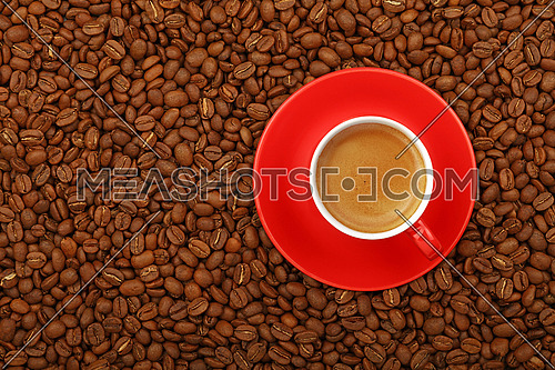 Full espresso in red cup with saucer on background of roasted coffee beans, elevated top view, close up