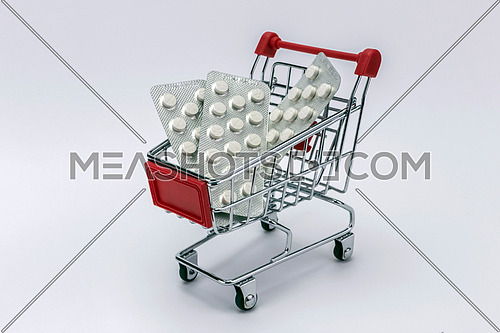 Shopping cart full of pills (isolated on white)