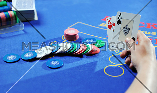 woman play black jack card game in casino on blue table