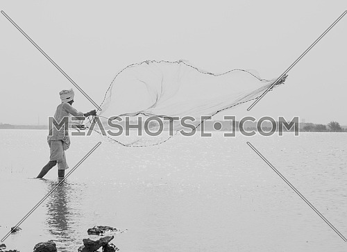 a black and white image of a Sudanese fisherman throwing a large fishing net.