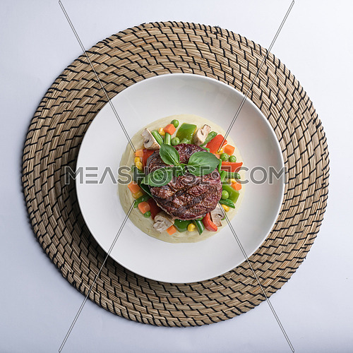 Thick cut beef filet steak served with mashed potatoes, vegetables, and mushroom on white porcelain dish