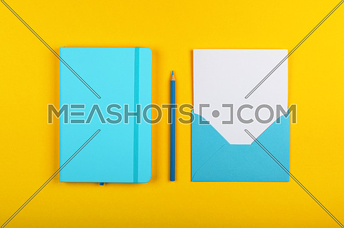 One open blank pastel blue envelope with white paper, closed notebook and wooden pencil over vivid yellow background, flat lay, directly above