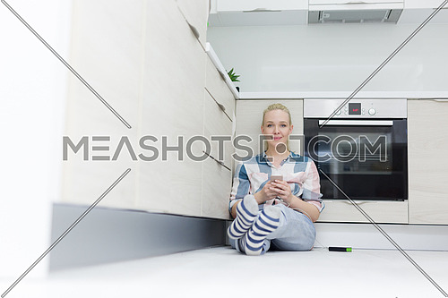 beautiful young women using mobile phone on the floor at modern kitchen