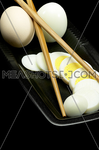 fresh boiled eggs one whole ,one peeled and another sliced on a black plate with chopstick