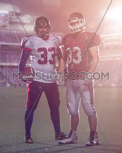 Two American football players standing  on the field of big modern stadium with flares and lights