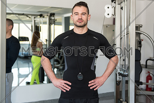 Personal Trainer Wearing Sportswear And Standing In A Gym Or Fitness Club Center