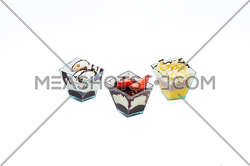 Three cupcakes with chocolate,white chocolate, fruits,cream and custard in a plastic cup,isolated on white background.