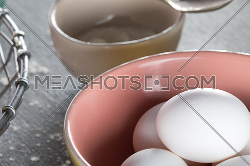 Eggs in a pink yellow bowl aside beige bowl with flour in it
