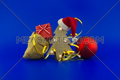 Christmas tree with red Santa hat and jute sack with gift boxes on a festive blue background. New Year and Christmas gift season concept