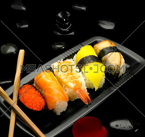 assorted sushi plate on black pebbles over black background