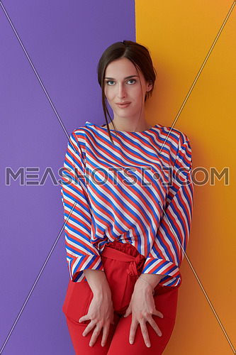 Portrait of young woman posing in the studio. Female model standing over a purple and yellow background. Concept of fashion and beauty