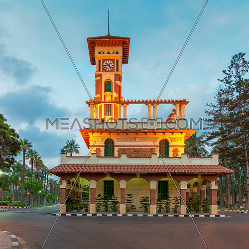 Facade of the clock tower in Montaza public park with decorated stone wall, green wooden window shutters, and red tile canopies at sunrise time, Montaza public Park, Alexandria, Egypt