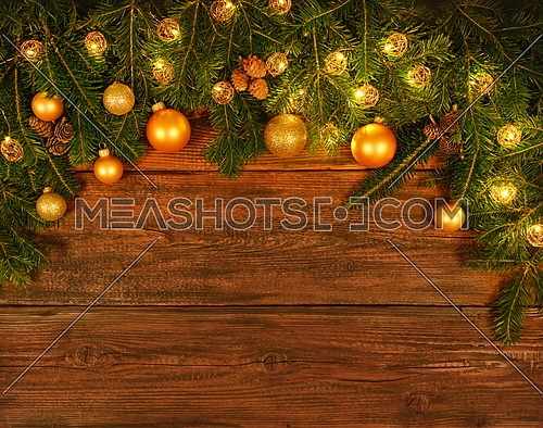 Close up fresh green spruce or pine Christmas tree branches with cones, lights, golden, balls and baubles decoration, over dark brown wooden planks background with copy space