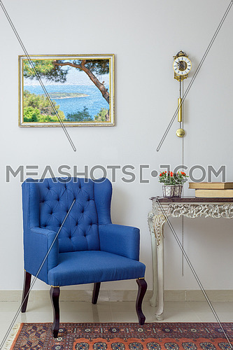 Vintage Furniture - Interior composition of retro blue armchair, vintage wooden beige table, and pendulum clock over off white wall, tiled beige floor and orange ornate carpet