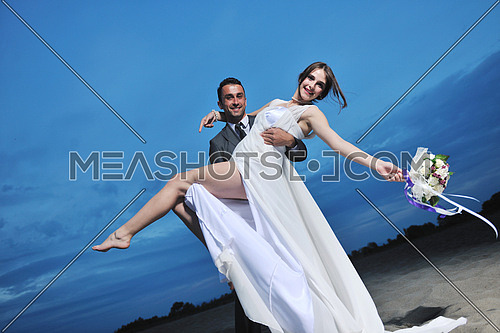 happy just married young couple celebrating and have fun at beautiful beach sunset