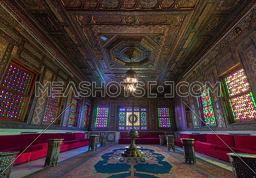 Manial Palace of Prince Mohammed Ali - Open for public. Syrian Hall with ornate wooden wall and ceiling, windows with colored stained glass and Ottoman Empire logo, Cairo, Egypt