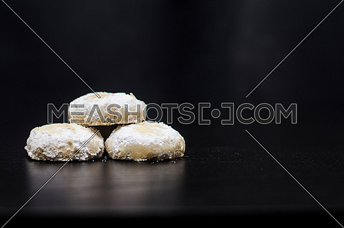 3 kahk (cookies) on a black table