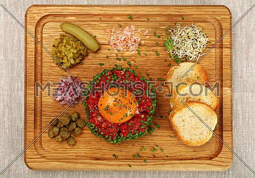 One portion of raw minced beef meat tartare steak with egg yolk, onions, cucumbers, capers, salt and toasts served on wooden board, close up, elevated top view, directly above