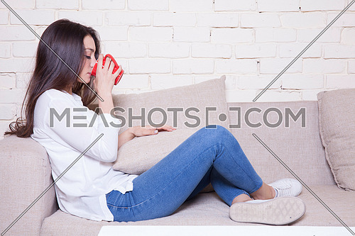 A girl sitting on a couch drinking coffee