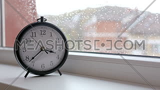 Old retro clock against window glass with rain drops