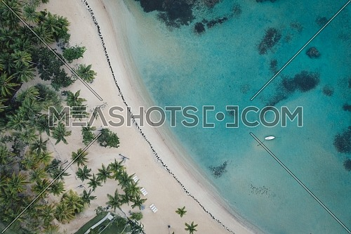 Drone shot of tropical beach with white boat anchored.Samana peninsula,Bahia Principe beach,Dominican Republic.
