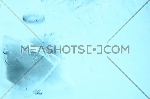 Clear ice cubes appear dropped down and float up with bubbles of air and melt in blue transparent water, extreme close up, low angle side view