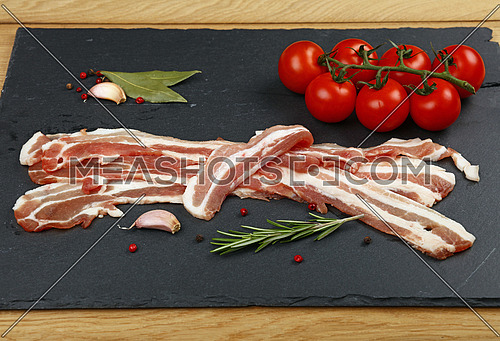 Raw pork bacon slices, rashers, spices, peppercorns, garlic, bay laurel leaves and red fresh cherry tomatoes on black slate board, close up, high angle view