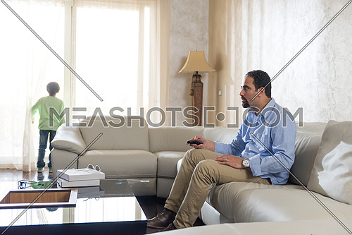 Middle Eastern father cheerfully spends time with his son on the sofa and enjoy watching tv