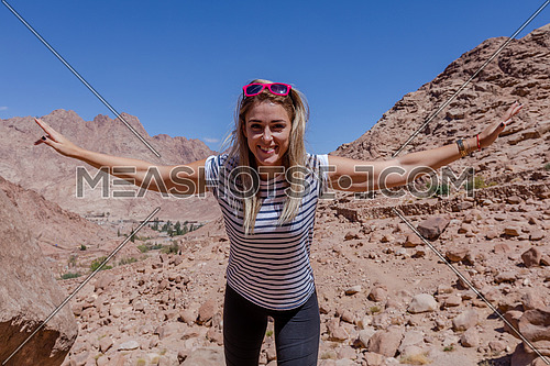 long shot for a female tourist wearing a pink Glasses and travel backpack climbing a big rock to explore Sinai Mountain for wadi Freij at day.