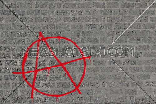 Concrete block wall with anarchy in red sprayed on it in red, illustration for urban background