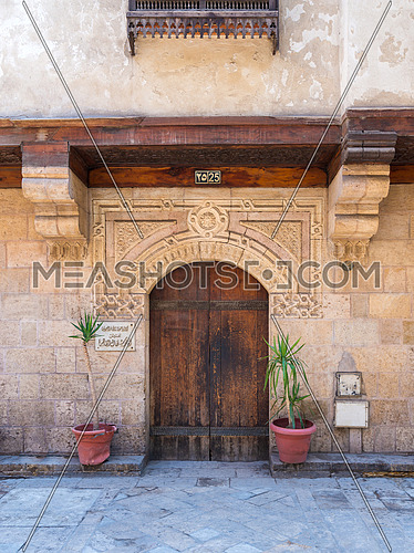 Facade of old stone bricks decorated wall with arched wooden door, Entrance of old Ottoman historic house of Moustafa Gaafar Al Selehdar, Moez Street