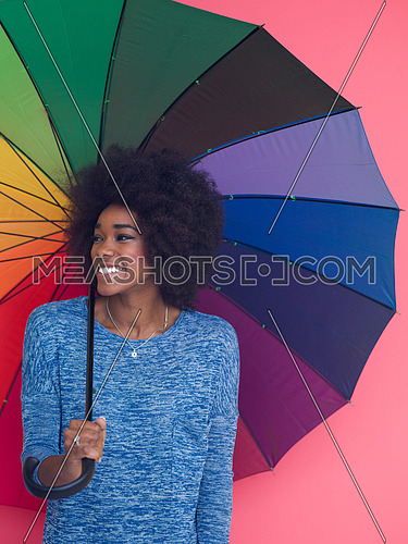 Portrait of young beautiful african american woman holding a colorful umbrella isolated on a Pink background