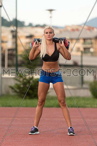 Young Woman Doing Bag Squat Exercise Outdoor