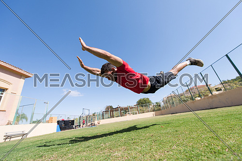young middle eastern man athlete enjoys doing the extreme push-ups outside