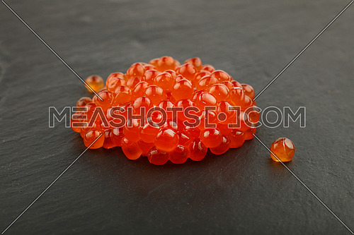 Close up one heap portion of salmon fish red caviar on background of black slate kitchen board, high angle view