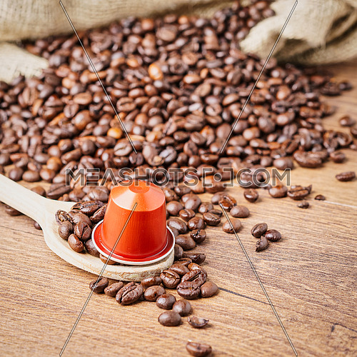 In the foreground a coffee capsule on wooden spoon and  roasted coffee beans with burlap sack on blur wooden background,top view.
