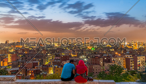 tow Couple  enjoy a visit to the city of Cairo and a spectacular view of the top of Al-Azhar Park in Salah Salem and in front entire Cairo at sunset