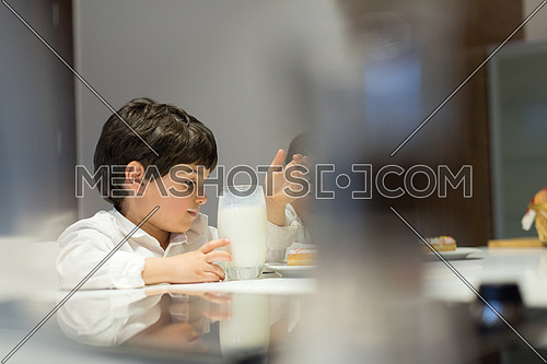 little middle east boy in the kitchen eating a snack and drinks milk with pleasurelittle middle east boy and girl eating snacks and drinking milk in the kitchen with pleasure