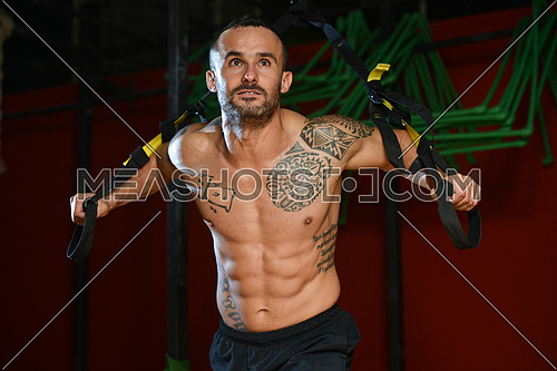Attractive Man Does Crossfit With Trx Fitness Straps In The Gym's Studio