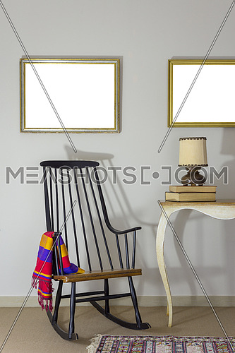 Interior shot of classic rocking chair and wooden ornate brown desktop photo frame on old style vintage table on background of off white wall with two hanged paintings with clipping path for paintings