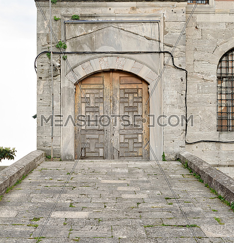 Stone tiled ramp leading to a wooden aged door over a stone wall of one of the small buildings attached to Sultan Ahmed Mosque (Blue Mosque), Istanbul, Turkey