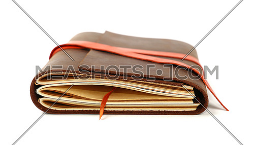 Close up of one vintage style jotter notebook with old leather cover and orange bookmark strap, isolated on white, low angle view