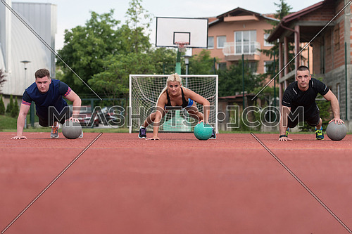 A Group Of Young People In Aerobics Class Performing Push-Ups On Medicine Ball Exercise Outdoor